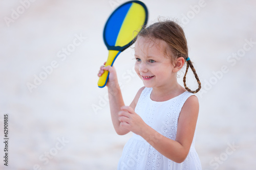 Little girl playing beach tennis