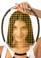 Young female tennis player looking through strings of racket