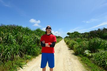 久高島の綺麗な自然と走る男性