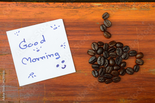 coffee beans and good morning note on the wooden background