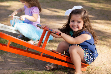 Cute little brunette in a seesaw