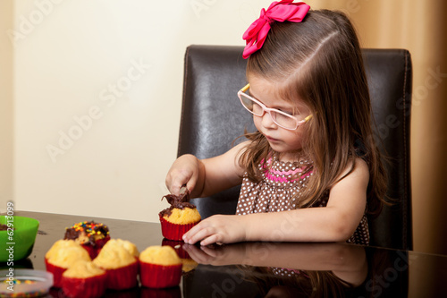 Beautiful girl decorating cupcakes