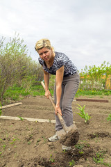 Young woman digs up beds in the garden