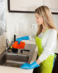 Young housewife cleaning pipe with detergent
