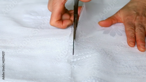 Close up of hands with scissors cutting white fabric