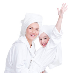 happy mother and young daughter in white dressing gown