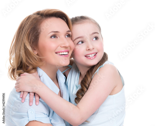 Smiling mother and young daughter looking up