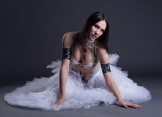 Seductive young belly dancer posing at camera
