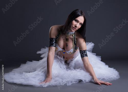Seductive young belly dancer posing at camera