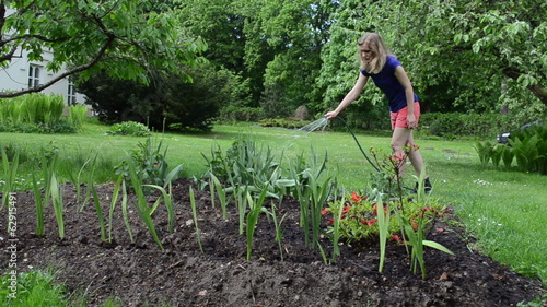 Pretty woman in shorts watering flower bed with hose in garden