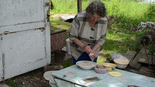 Senior woman prepare traditional food with potatoes and meat