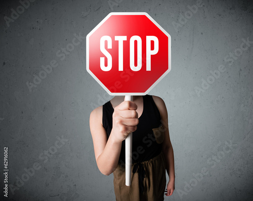Young woman holding a stop sign