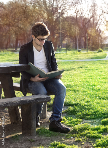teenager reading book in park