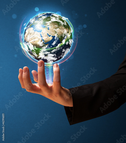 Businessman holding a glowing earth globe