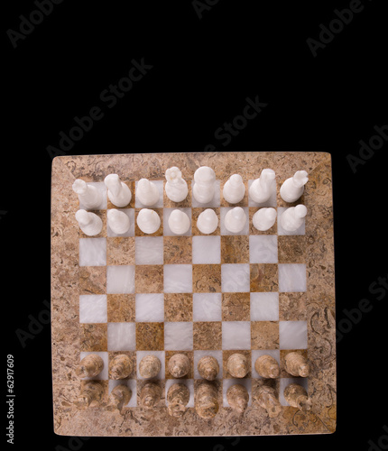 Stone made chess set on black background