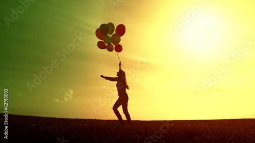 Beautiful female Silhouette Running Free Balloons