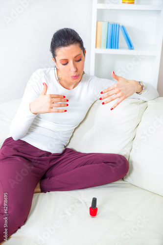 Pretty woman in bed applying nail polish