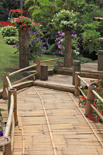 A wooden path among flower beds