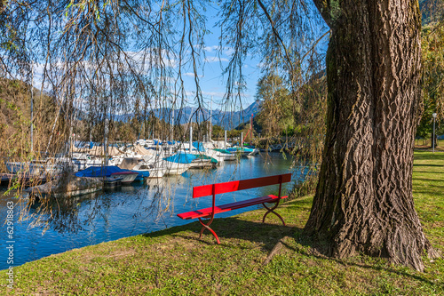 Red bench on lakeside of Lake Maggiore, Switzerland.