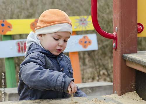 Child at playground playing with sand