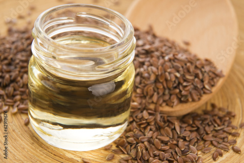 Linseed oil and flax seeds on wooden background