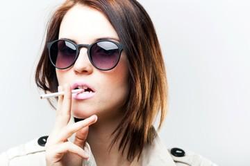 Elegant woman with sunglasses smoking cigarette