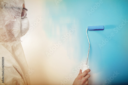Painting wall blue wearing protective clothes