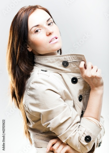 Fashionable young woman in white coat