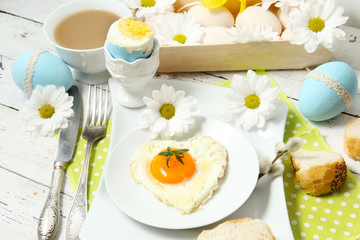 Easter table setting with flowers and eggs on old wooden table