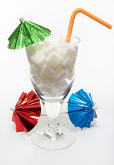 Drink with sugar cubes, umbrellas and straw