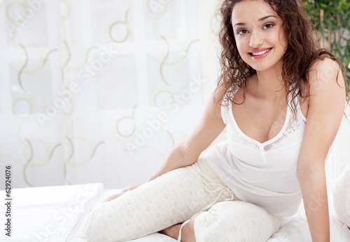 happy young woman siting in bed in white pajamas