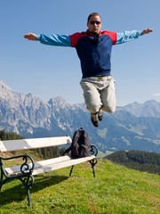 jumping man in front of mountain landscape