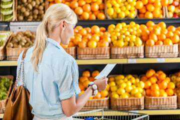 Girl looks through shopping list near the pile of fruits