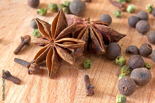 Anise with spices on wooden cutting board.