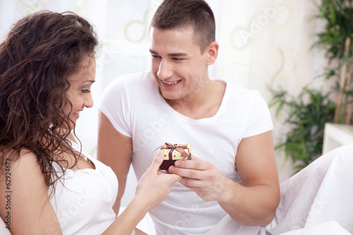 romantic couple in bed with gifts