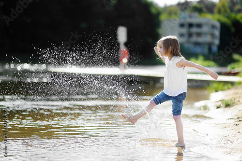 Little girl having fun by a river