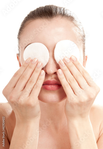Woman removes eye makeup with a cotton disk. Isolated on white b