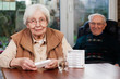 Leinwanddruck Bild Elderly woman with dispenser