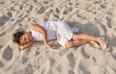 portrait of a little girl lying on the beach