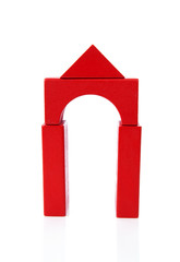 House made out of red wooden building blocks over white backgrou