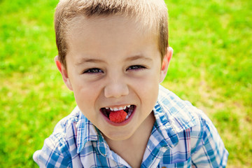 Funny boy eating raspberry