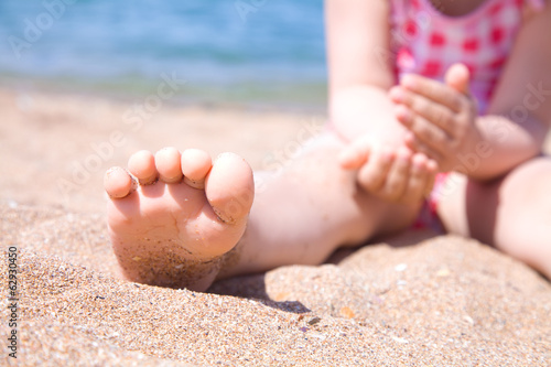 child's foot is close to the beach