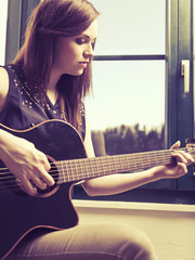 Playing acoustic guitar by the window