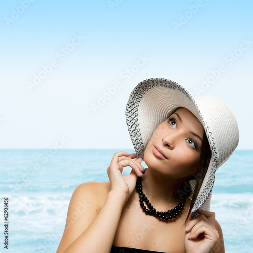 Pretty young woman holding her hat on her head