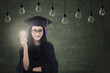 Attractive female graduate holding lit bulb under lamps