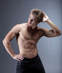 Attractive muscular man posing with naked torso