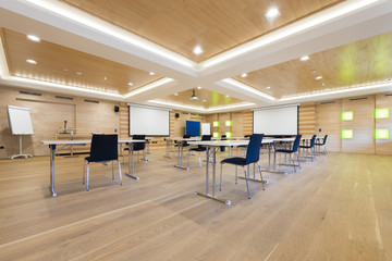 flipchart and projection screens in wooden conference room