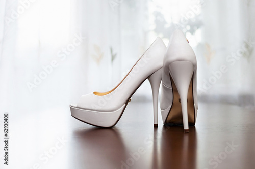 white wedding shoes for women on the floor