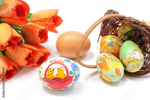 Easter eggs in overturned basket and fresh egg with tulips