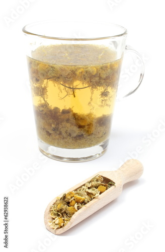 Dried chamomile on wooden spoon and cup of beverage